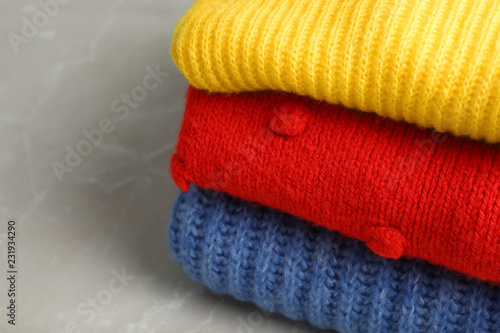 Fotografía  Stack of folded knitted sweaters on table, closeup