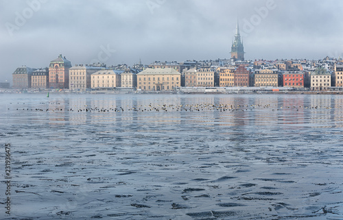 Foto  Frozen bay and Stockholm gamla stan on a foggy winter morning.