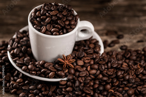 White cup covered coffee beans with star anise