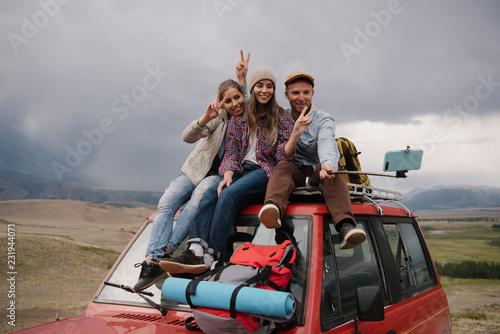 Travelers posing for selfie on car
