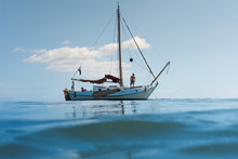 Sailboat Floating On Calm Day Out On The Ocean.