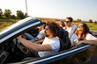 Group of young beautiful girls and guys in sunglasses smile and ride in a black cabriolet on the road on a sunny day.