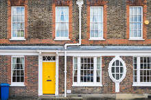 Facade Of Classic British Brick House With Colored Doors And White Wooden Windows