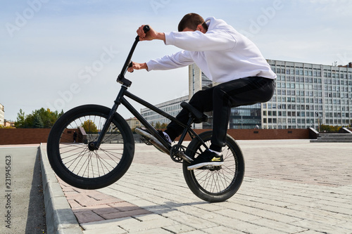 Photo Full length portrait of modern teenager doing stunts on bmx bike in skateboardin