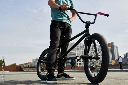 Fototapeta Low section portrait of unrecognizable young man standing by bmx bike  in extrem