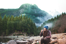 A Woman Enjoys A Hot Beverage On The Shore Of A Rugged Wilderness Mountainside Lake