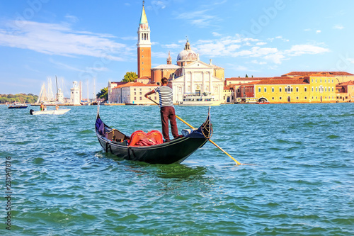 Fotografering A venetian gondolier sailing to San Giorgio Maggiore island