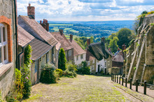 Bright Scenic Landscape View Of The Rolling Green Countryside From The Cobblestone Street Of A Traditional English Village