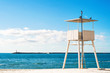 Panoramic view of white wooden lifeguard tower or station at blue sea and sky background
