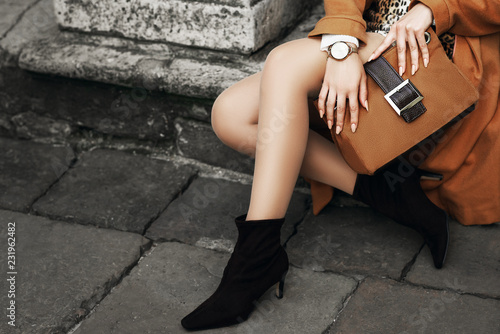 Street fashion details of elegant outfit: woman wearing wrist watch, ankle sock boots, holding light brown, camel color suede handbag, posing in street of european city Canvas Print