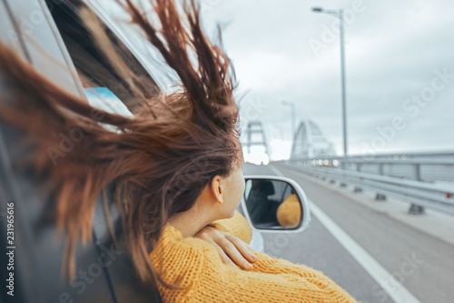 Fototapeta  Girl in car looking forward on a bridge at weekend road trip