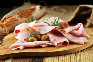 Fototapeta Sliced ham on wooden background. Fresh prosciutto. Pork ham sliced.