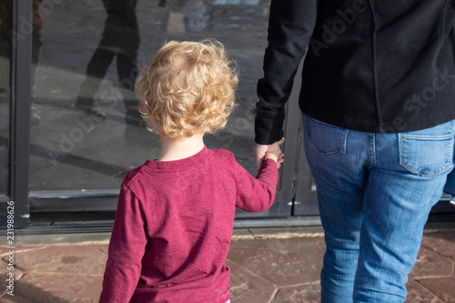 Slika na platnu Shopping - Cropped back view-Young blond curly headed child holding hand of moth