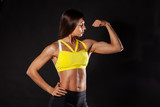 female bodybuilder showing her biceps isolated on black background