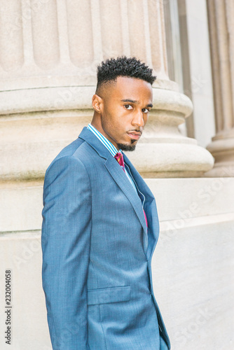 73e2ef0a56 After work. Young African American Businessman with beard, short afro hair,  working in New York, wearing dark sky blue suit, violet red patterned tie,  ...