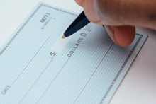 Writing A Check With Blue Pen On White Background
