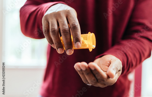 Fotografia african american man in red shirt pouring pills from prescription pill bottle