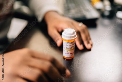Fotografia  african american man taking opioid pills sitting at a dark table
