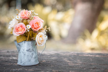 Roses In A Jug On A Wooden Table