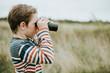 Leinwandbild Motiv Young boy looking through a pair of binoculars
