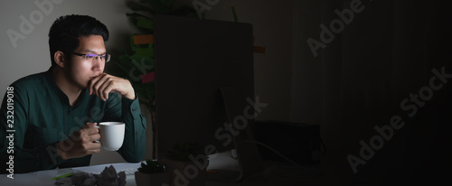 Fototapeta Banner of attractive young asian man drinking coffee sitting on desk table looking at laptop computer in dark late night working feeling serious thinking and determinated at home office concept. obraz