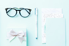 Flatlay Of Paper, Pen, Reading Glasses And Little Gift Box On A Blue Background