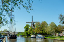 A Classic Dutch Windmill In The City Of Dokkum, Friesland, In The Northern Parts Of The Netherlands, As Seen On A Bright Sunny Spring Afternoon
