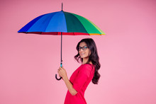 Beautiful Brunette Girl In The Studio On A Pink Background In The Style Dress With Rainbow An Umbrella