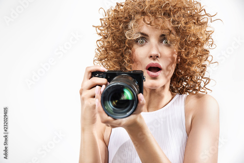 Portrait of a redhead woman holding a camera