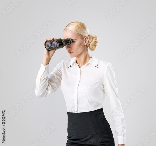 Elegant businesswoman looking through the binoculars
