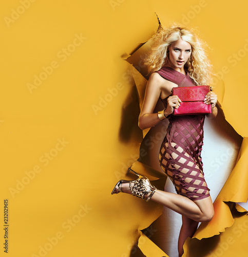 Shopping concept - blond lady jumping through the wall hole