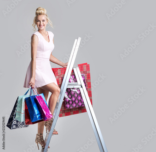 Blond, beautiful lady holding a bunych of shopping bags, standing on a ladder