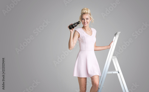 Charming blonde holding binoculars and standing on a ladder