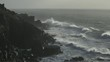 Cinematic wide shot of waves battering the cornish coast