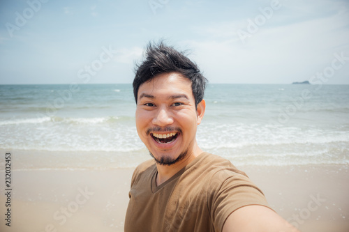 Foto  Cheerful and happy face of man selfie himself on the beach.