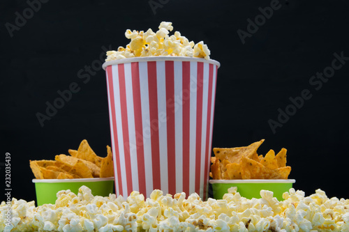 Papiers peints Buffet, Bar bar snack for a cinema, on a black background a bucket of nachos and a glass of popcorn