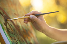 Artist Drawing A Picture On An Easel In Nature, A Hand Makes A Brush Stroke On A Canvas, A Concept Of Creativity And A Hobby