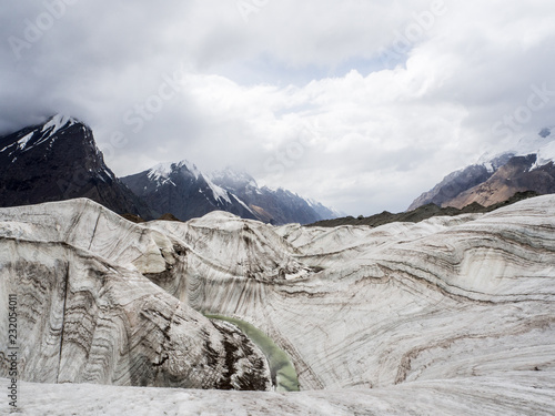 Glacier and river landscape with interesting ice texture and mountains
