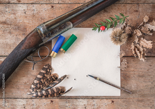 Foto op Canvas Jacht Beautiful hunting season still life/ vintage hunting rifle, cartridges, vintage pen on the target with traces of bullets, pheasant feathers on old wooden background