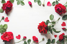 Red Roses Flowers And Hearts On A White Wooden Background, Copy Space, Top View. Festive Romantic Background For Valentine's Day