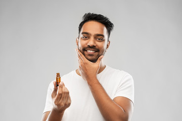 Fototapeta grooming and people concept - smiling young indian man applying lotion or beard oil over gray background