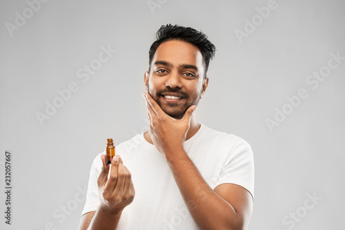 Obraz na plátne grooming and people concept - smiling young indian man applying lotion or beard