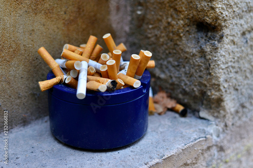 Blue ashtray full of cigarette butts on stone window Canvas Print