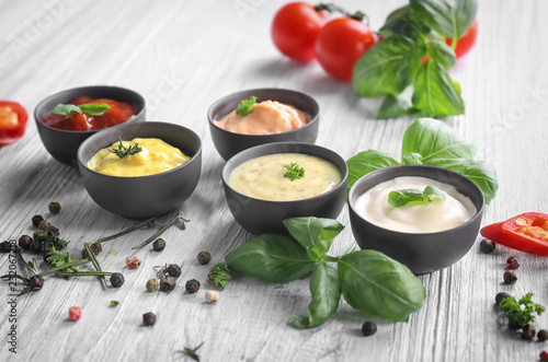 Different tasty sauces in bowls with spices on light wooden table