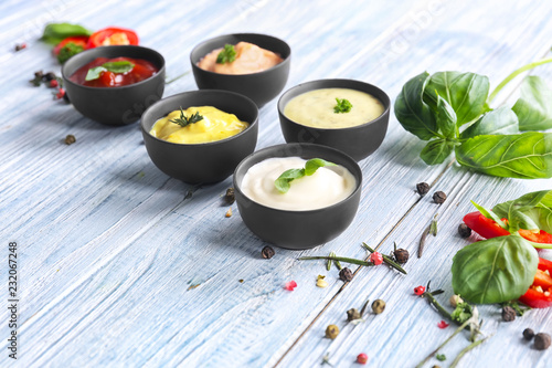 Fotomural Different tasty sauces in bowls with spices on light wooden table