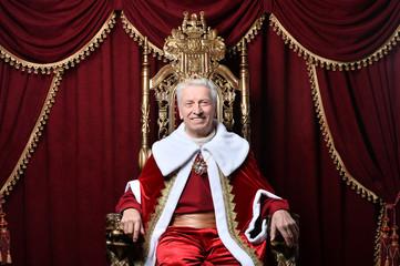 Portrait of confident senior man in red cloak