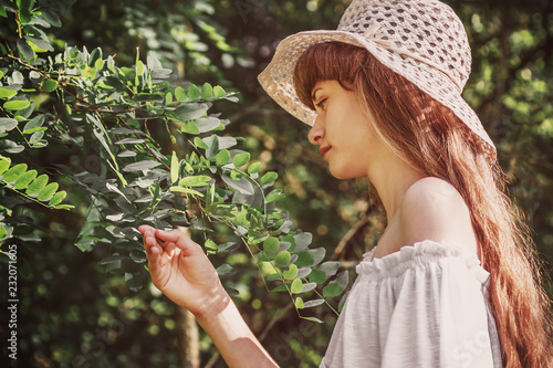 Fényképezés  Outdoor portrait of young beautiful smiling girl with long hair, wearing straw hat, posing near blooming tree