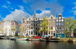 Facades row of old historic Houses over canal water with spring green trees, Amsterdam, Netherlands