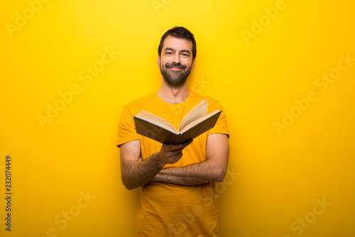 Fotografía  Man on isolated vibrant yellow color holding a book and giving it to someone