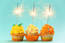 Tasty Birthday Cupcakes With Sparklers On Color Background